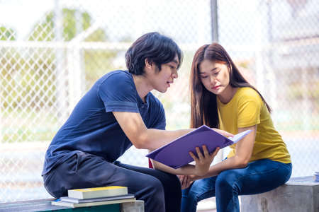 On a campus, a couple of students are studying together, and a teenager sits on a seat beside a sports court with a book. 免版税图像