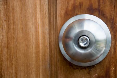 Doorknob silver stick blacked beautiful brown wooden door. Stock Photo
