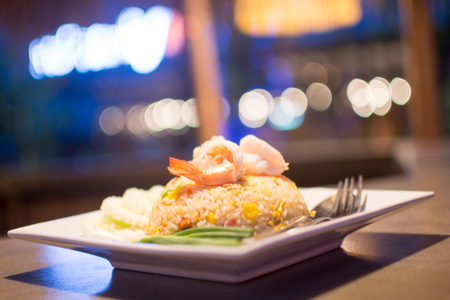 the distinguished: Shrimp fried rice dish is placed on a wooden table. Appetizing beautiful bokeh background blur look distinguished.