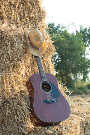 guitar resting on straw Division in the fields, the warm sun of farmers placed players relax after work.