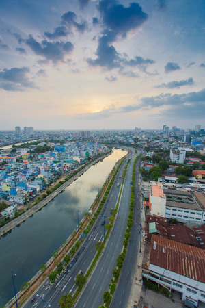 HO CHI MINH CITY  VIETNAM - DEC 13 2014: curve of Ho Chi Minh Riverside cityscape night view with Ben Nghe or Tau Hu canal and calmet Bridge in sunrise or sunset Editorial