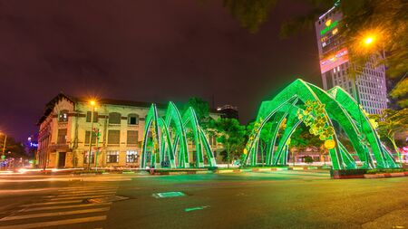 Ho Chi Minh City, Vietnam  - December 19 2014 : Green welcome gate on the main street at downtown of Ho Chi Minh City, Vietnam on Christmas Eva and Happy New Year and Lunar New Year ( TET Holiday)