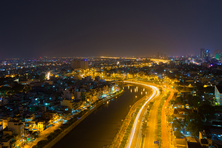 Ho Chi Minh City, Vietnam - December 14 2014: curve of Ho Chi Minh Riverside cityscape night view with Ben Nghe or Tau Hu canal and calmet Bridge in sunrise or sunset Editorial