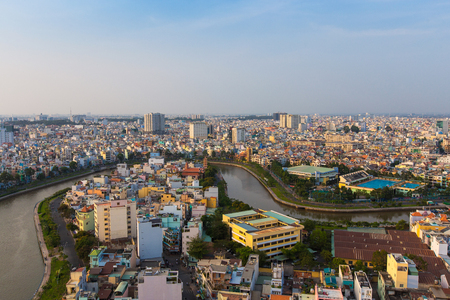 loc: Ho Chi Minh City, Vietnam - January 25 2015 : Saigon riverside with the road across the Nhieu Loc canal and houses, Ho Chi Minh City, Vietnam. The shape look like trident of Poseidon