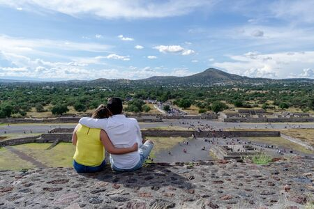 young couple watching the ruins of Teotihuacan from the top of the pyramid of the sun Stock Photo