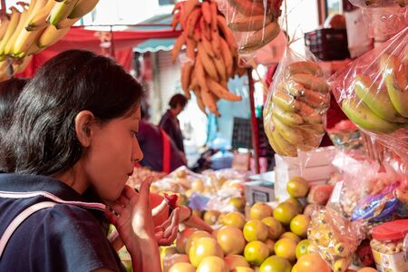Woman buying some vegetables and fruits in a local mexican market