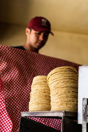 tortillas stacked on a tortilla machine and a while a man is covering them