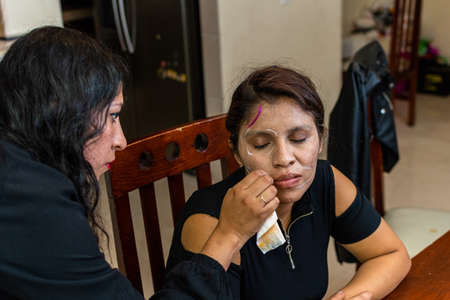 woman putting makeup on another woman for a party of the day of the dead