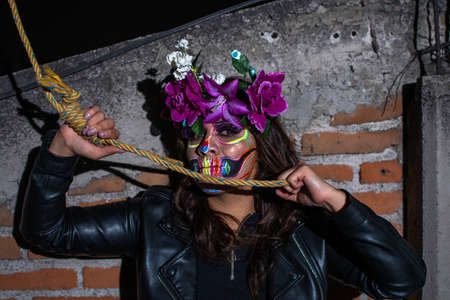 portrait of woman wearing a Dia de Muertos makeup with a rope around her neck Stock Photo