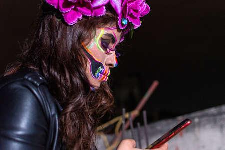 portrait of woman wearing a Dia de Muertos makeup looking something on her phone