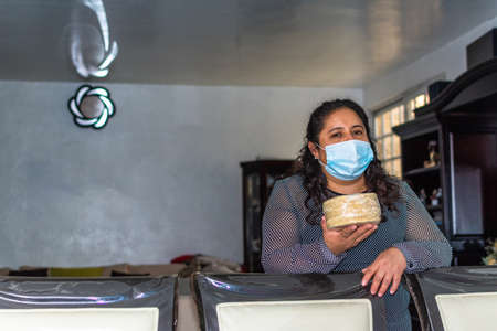 old woman wearing mask carrying some tortillas