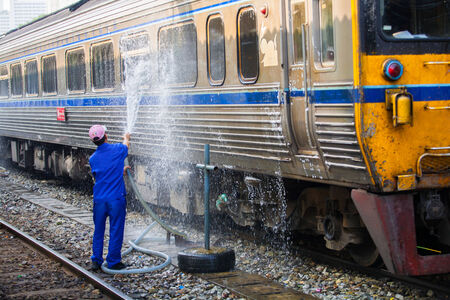 cleaning crew: Worker cleaning the train at station Thailand