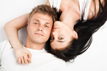 Happy young couple relaxing together while laying over white background photo