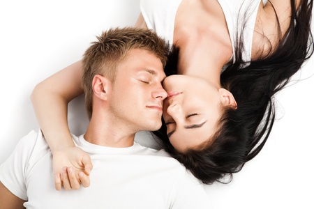 Happy young couple relaxing together while laying isolated over white background photo