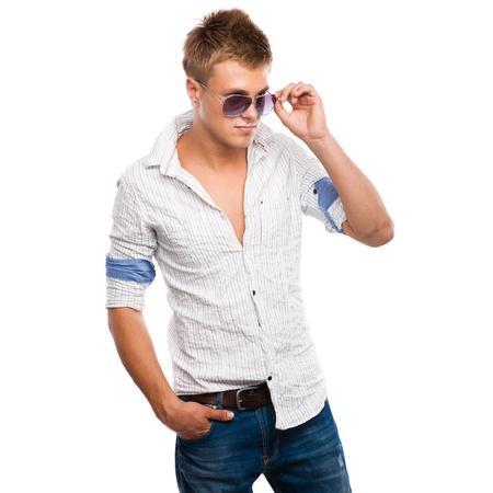 Beau jeune homme en jeans, chemise légère et lunettes de soleil isolé sur fond blanc