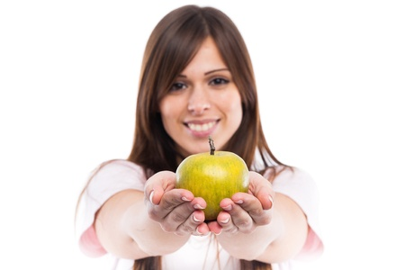Smiling young woman with apple isolated on white background. Focus on apple photo