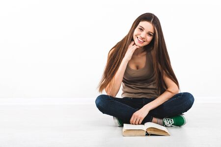Beautiful young woman sitting on floor with book photo