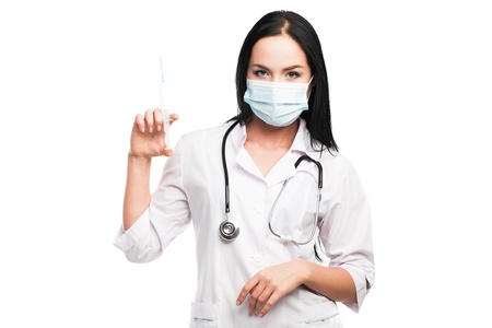 Medical doctor woman with a syringe on white background photo