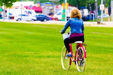 Curly-haired blonde woman walking in the park on a red bicycle