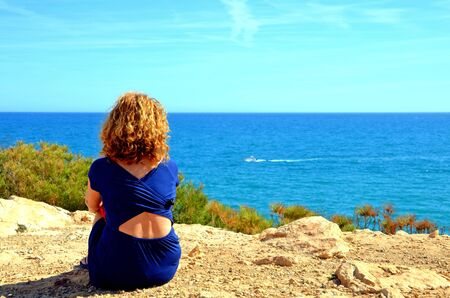 Blond woman in blue dress looking at the sea from a cliff near Torredembarra lighthouse