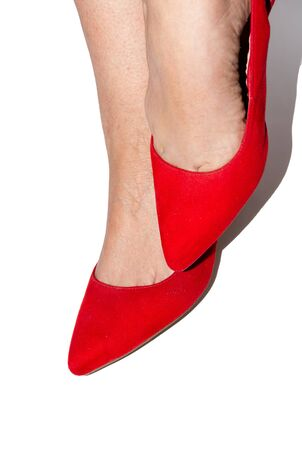 Woman feet with red shoes on white background Фото со стока