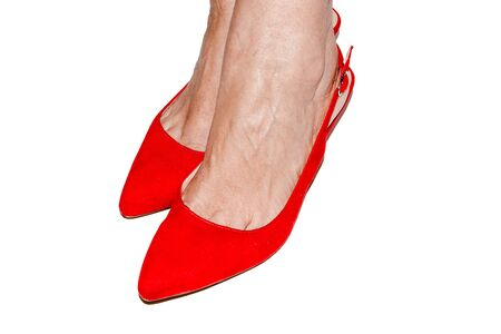 Woman feet with red shoes on white background Standard-Bild