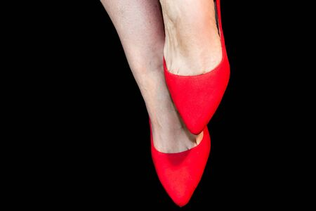Woman feet with red shoes on black background