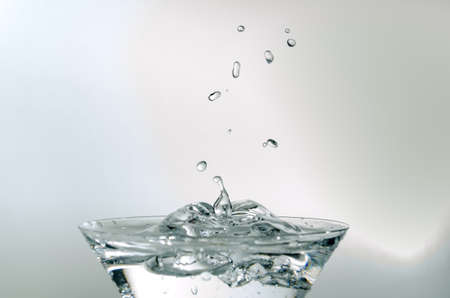 Close-up of water drop falling into a glass on white background Stockfoto