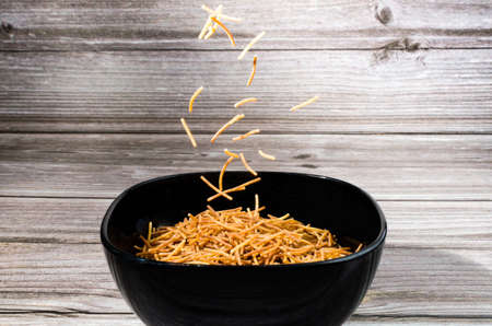 Close-up of cooked polyphosphate noodles falling into a ceramic bowl on a wooden table