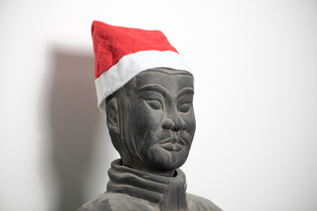 imperialism: Half profile of Chinese terracotta warrior stature waring santa hat, face, isolated on white background