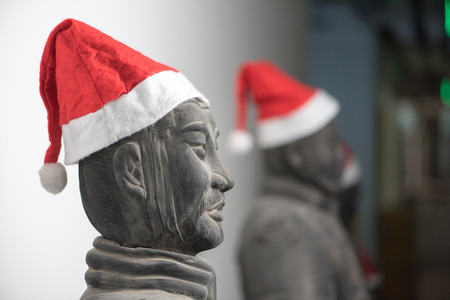 christmas military: Half profile of Chinese terracotta warrior stature waring santa hat, upper body, with more statues in the background, selective focus Stock Photo