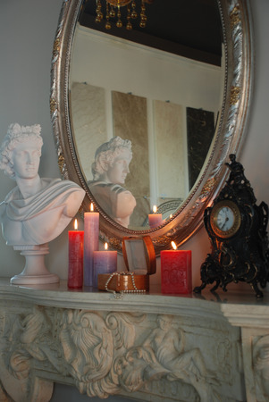 Bust of Apollo Belvedere is on the fireplace  Romantic setting, standing next candle box with a pearl necklace, classic vintage watch  photo