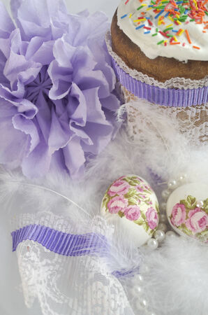 Easter composition of Easter cake, down, bow and painted eggs photo