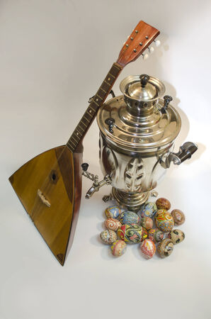 Easter eggs lie, standing next to the samovar and balalaika. Ukrainian Easter egg, decorated with traditional Ukrainian folk designs using a wax-resist (batik) method. photo