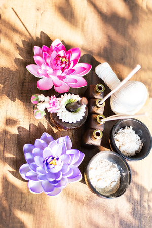 Spa still life with perfume bottle and lotus flower,Spa massage compress balls, herbal ball on the wooden with treaments spa , Thailand, select focus