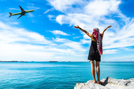Back side of traveler girl looking at the flying plane above the sea, travel and active lifestyle concept Banque d'images