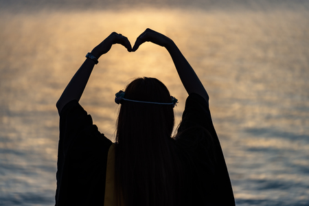 silhouette heart shape with hands on sunset,Silhouette hands making a heart shape,Heart concept, the concept of good health work.
