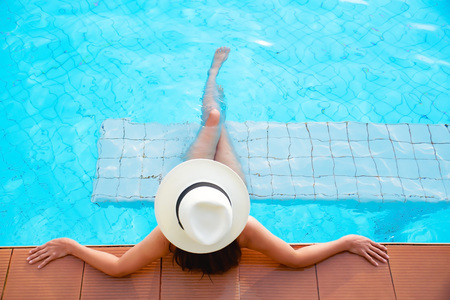 Young woman in big hat relaxing on the swimming pool  Stok Fotoğraf