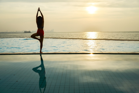 Silhouette young woman practicing yoga on swimming pool and the beach at sunset. Stock Photo