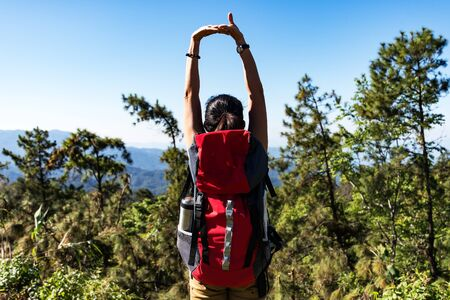 Hiker woman feeling victorious facing on the mountain, Thailand Banque d'images