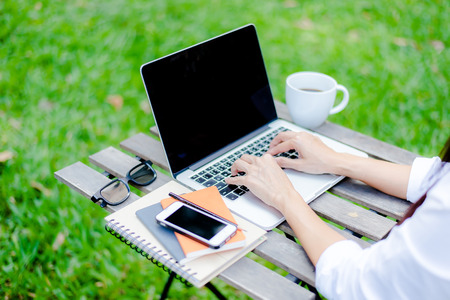 Freelance work. Casual dressed man sitting at wooden desk inside garden working on computer pointing with color pen electronic gadgets dropped around on table side view