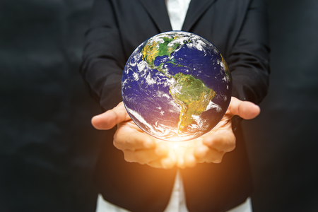 Earth in the hands isolated on black background. Stock Photo