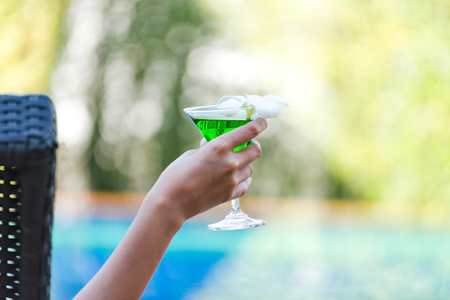 Woman in swimsuit relaxing with cocktail on chaise-longue Stock Photo