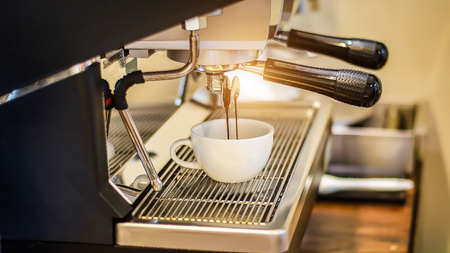 Coffee flowing into a cup from espresso machine Stock fotó