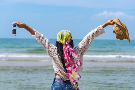 Happy woman stands at a beautiful beach and blue sky.