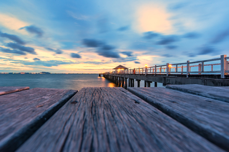 wood bridge to the sea at sunset.