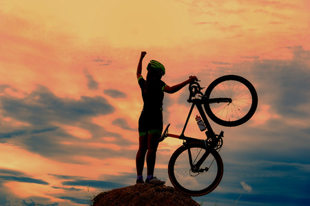 Silhouettes of biker-girl at the sunset