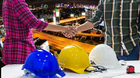 El equipo de ingenieros profesionales y el trabajador están sacudiendo las manos mientras que trabaja el control de seguridad, fondo de la ciudad. Concepto de construcción. Foto de archivo - 92032457