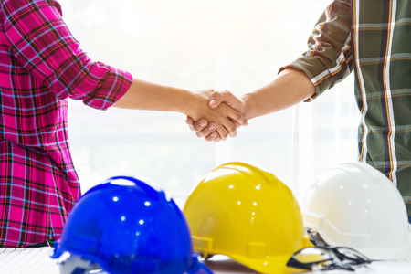 Team of professional engineers are shaking hands while working in the office center . ,occupational,safety,construction concept .
