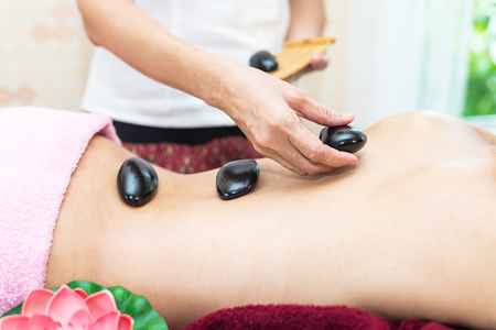 Back massage with hot stones.,Asia beauty woman lying down on massage bed with traditional hot stones along the spine at Thai spa and wellness center, so relax and lifestyle. Healthy Concept Фото со стока